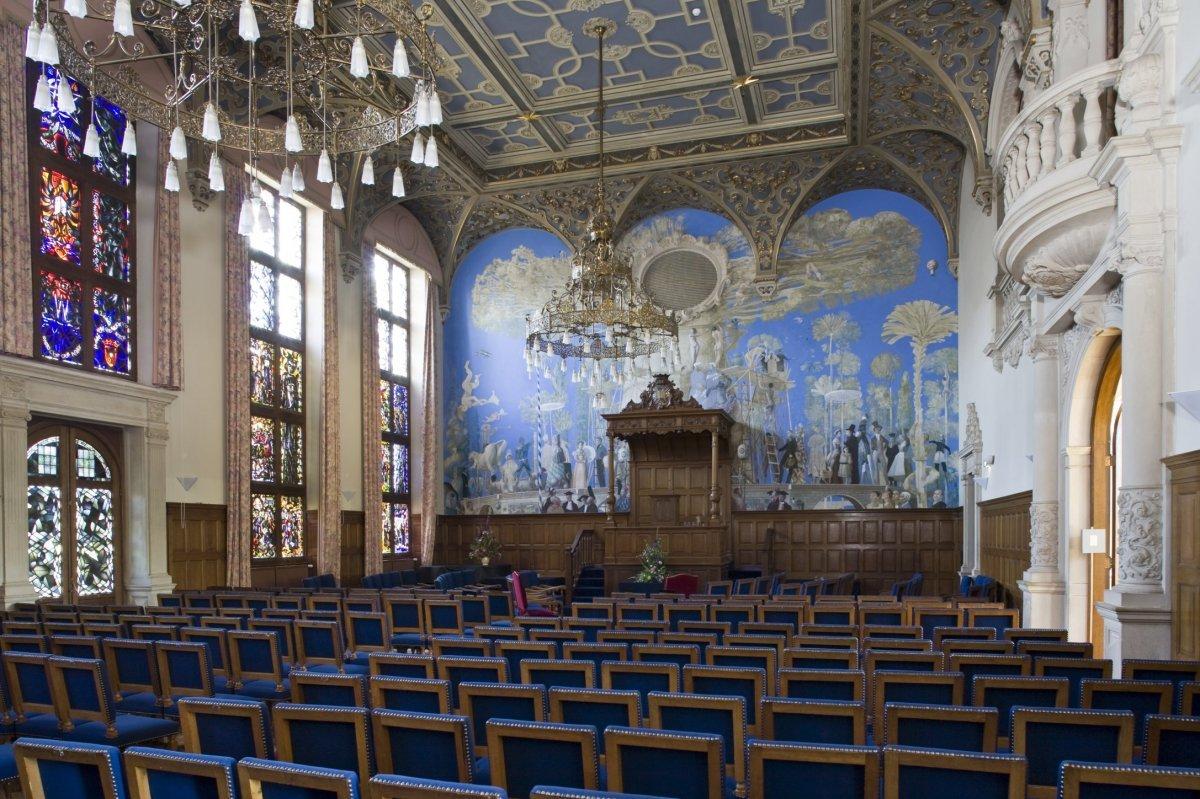 Het interieur overzicht van de Aula (Academiegebouw Groningen). De muurschildering 'De boom der kennis' (1987) is van de Groningse kunstenaars Matthijs Röling en Wout Muller. Bron Wikipedia